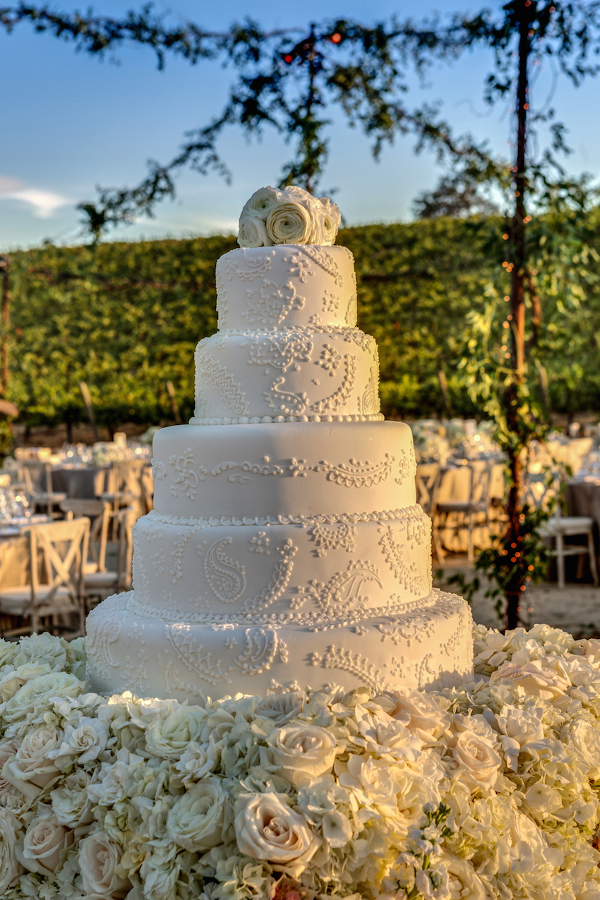 White wedding cake on blanket of rose, hydrangea, and gardenia flowers
