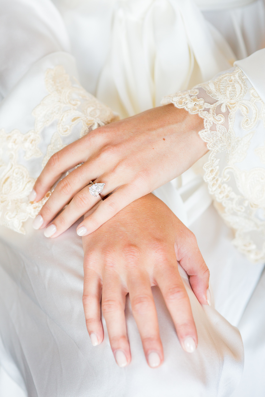 Bride with teardrop engagement ring and cream manicure