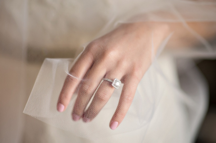 Pink wedding manicure behind bridal veil