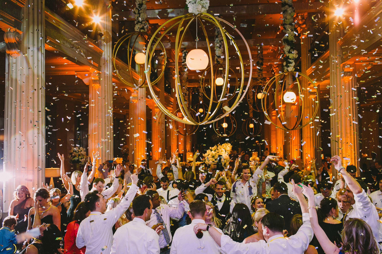 Wedding guests dancing under confetti