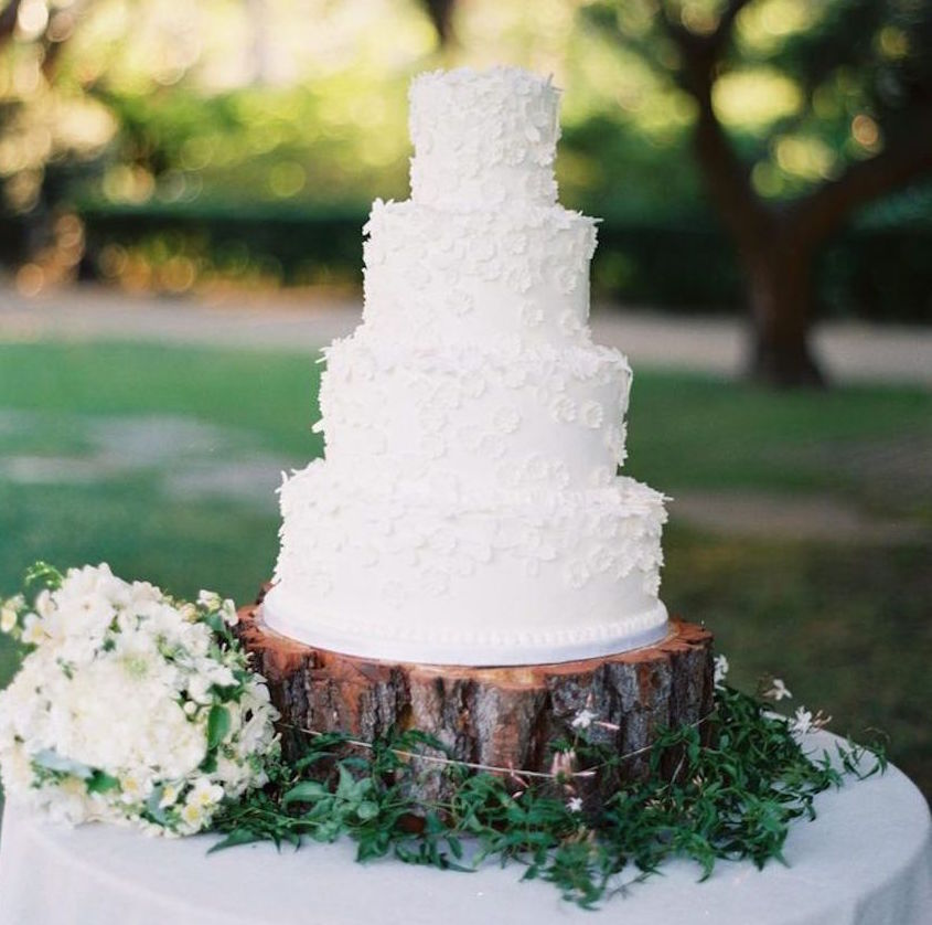 White wedding cake on tree trunk slab at outdoor wedding