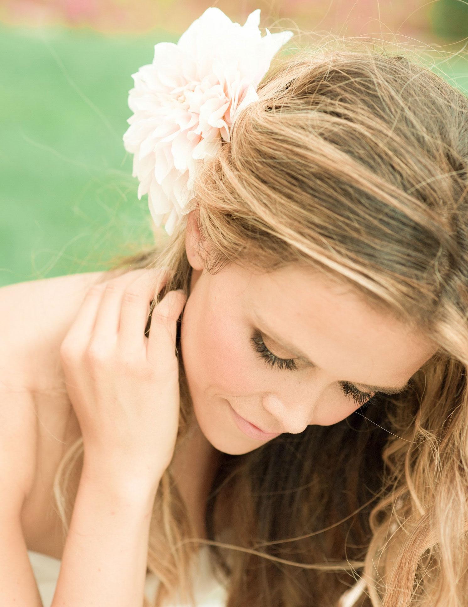 Fresh pink dahlia in Katrina Hodgson's wedding hair
