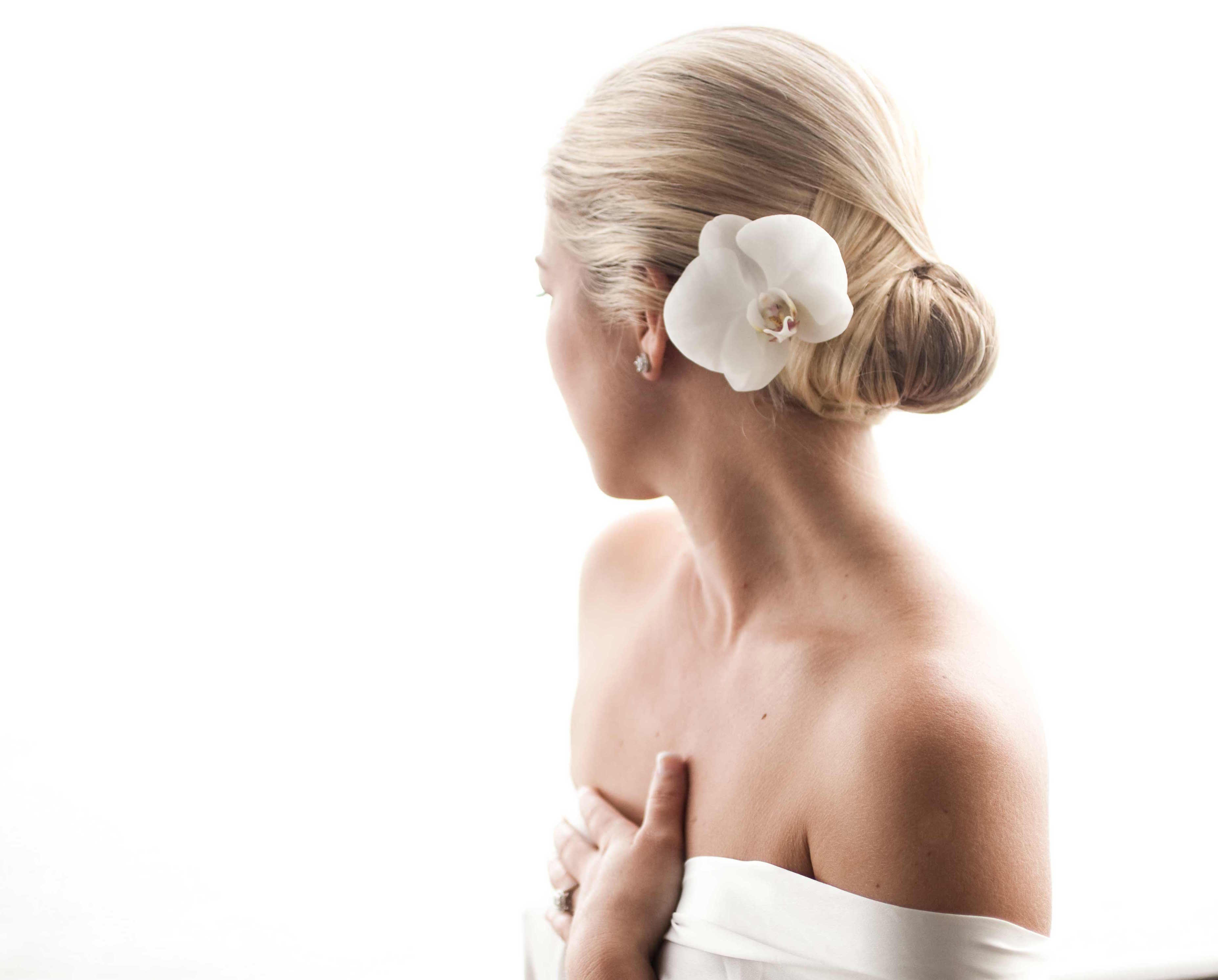 White orchid flower in bride's wedding hairstyle
