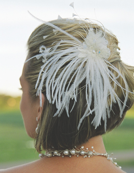 White feather hair accessory on bride