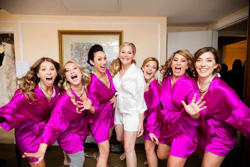 Bridesmaids in bright fuchsia silk robes