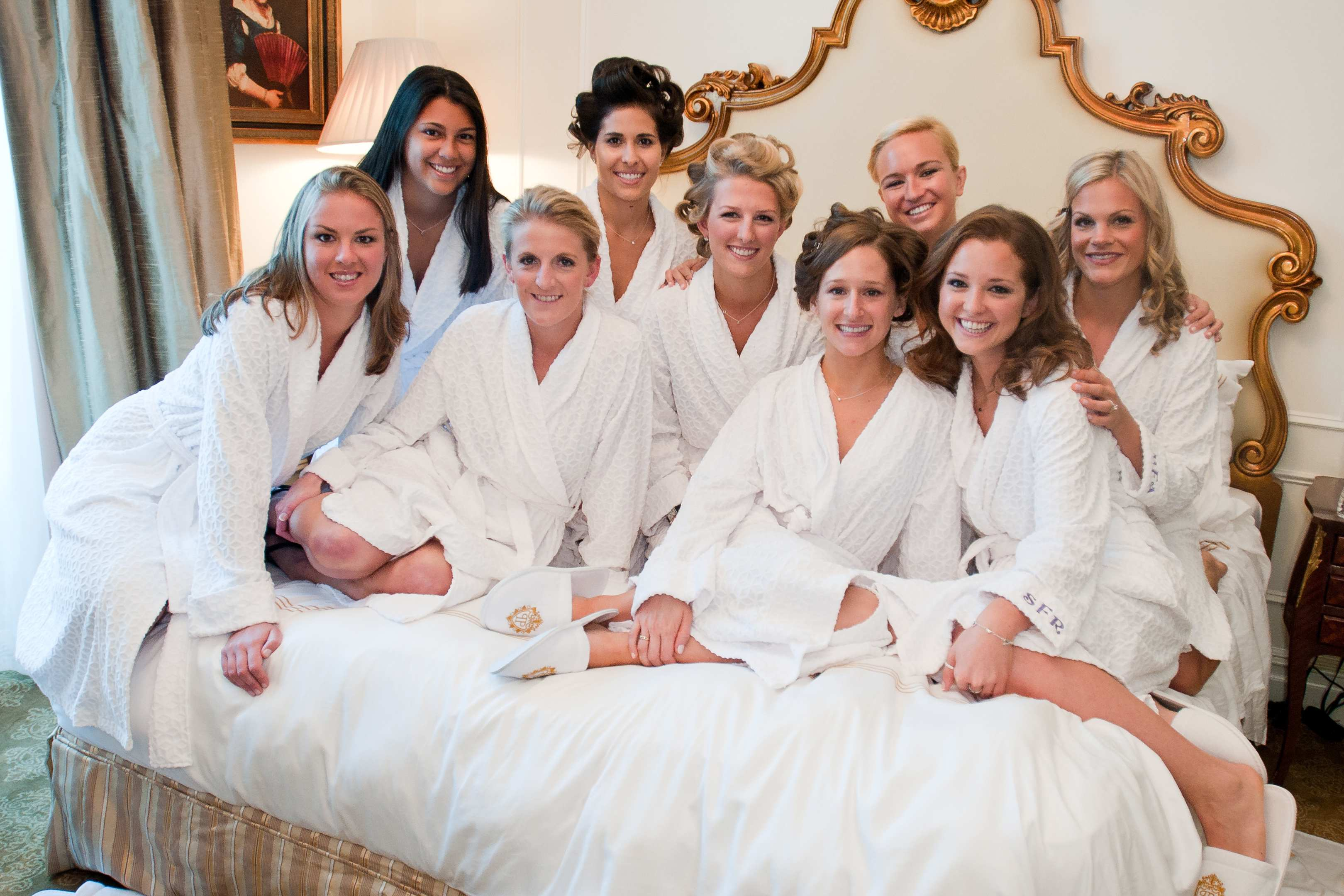 Bride and bridesmaids getting ready photos on bed with white robes