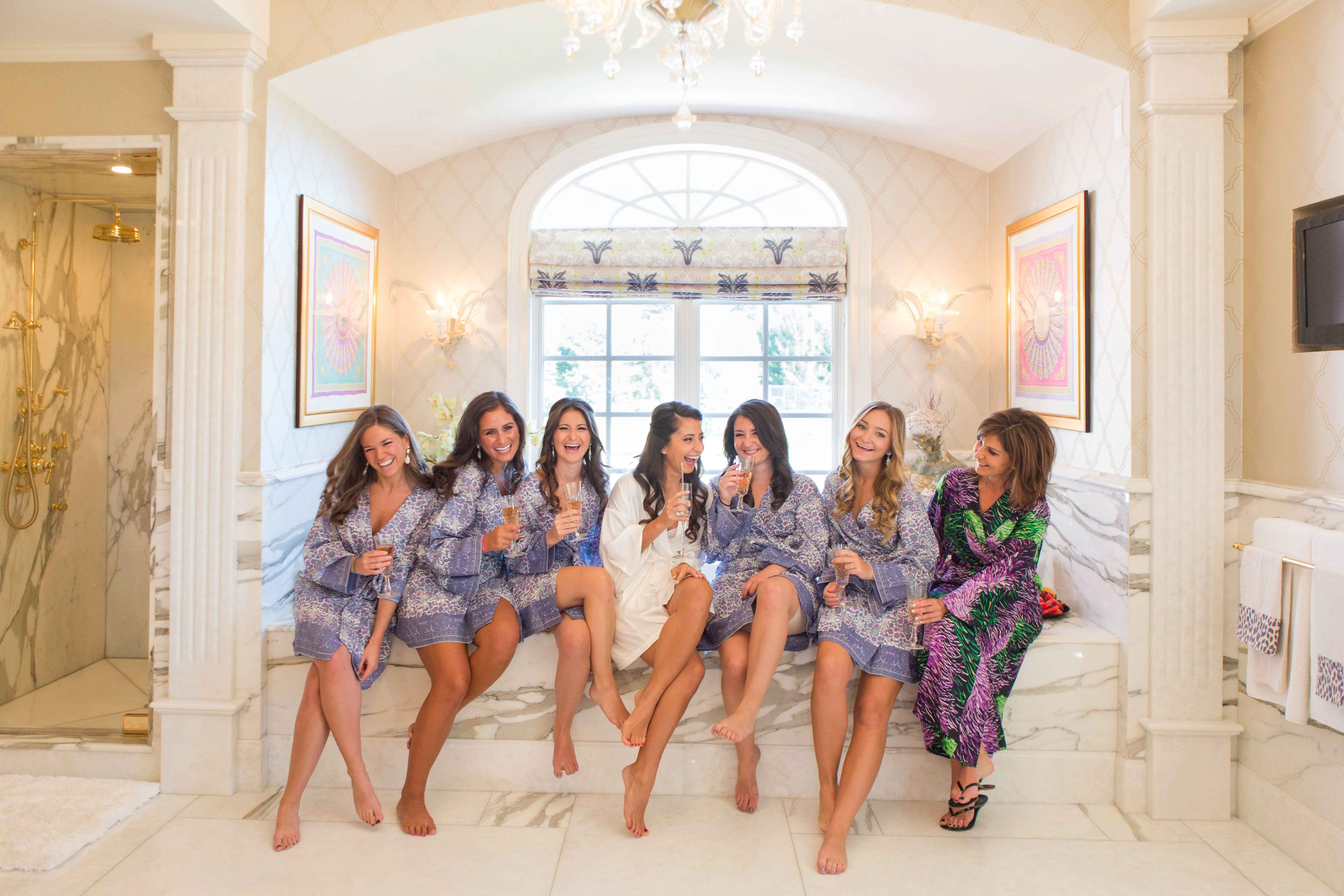Bridesmaids in marble bathroom in floral print robes