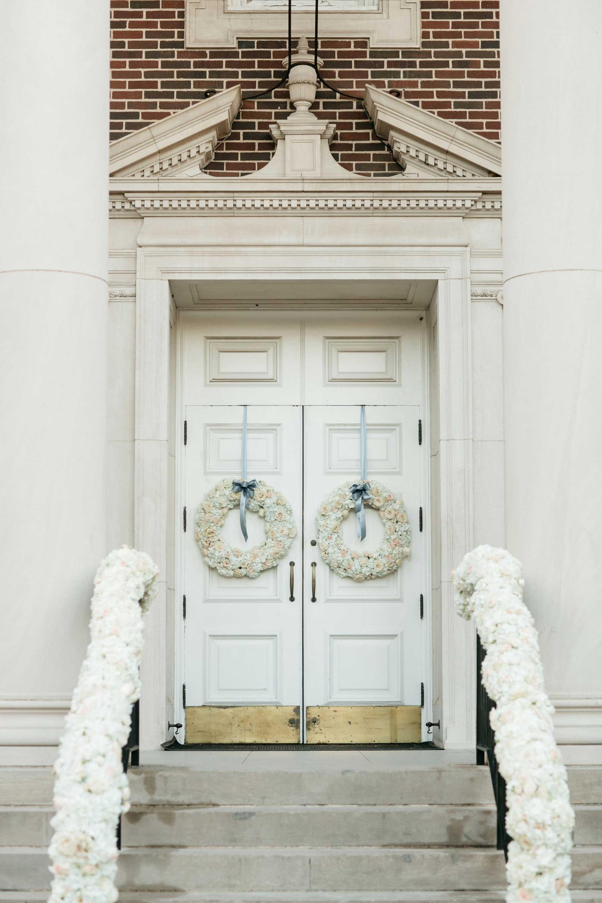 White flowers with blue ribbon on church wedding door