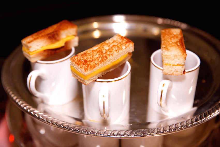 Mugs filled with soup and grilled cheese