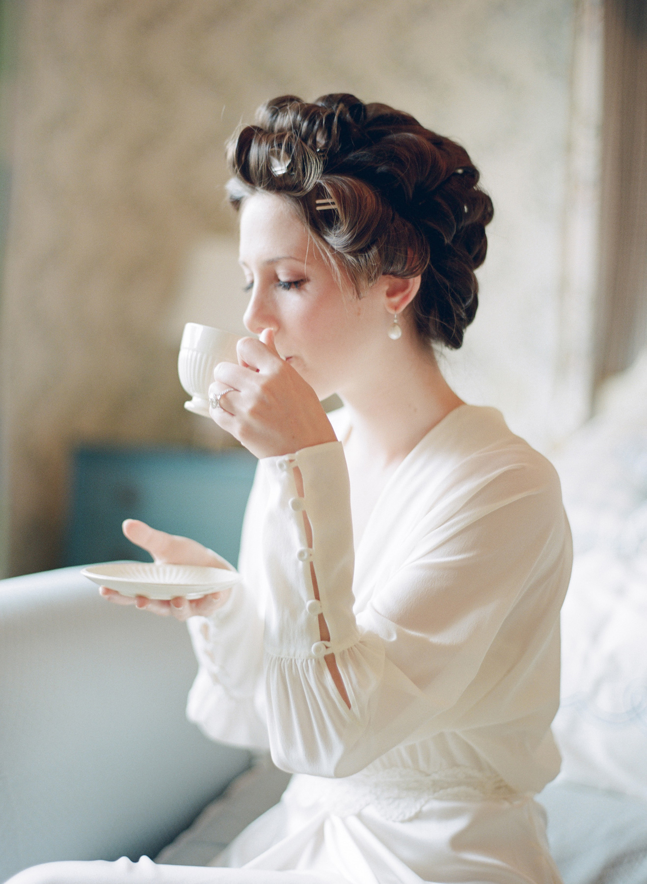 Bride in curlers sipping tea before wedding