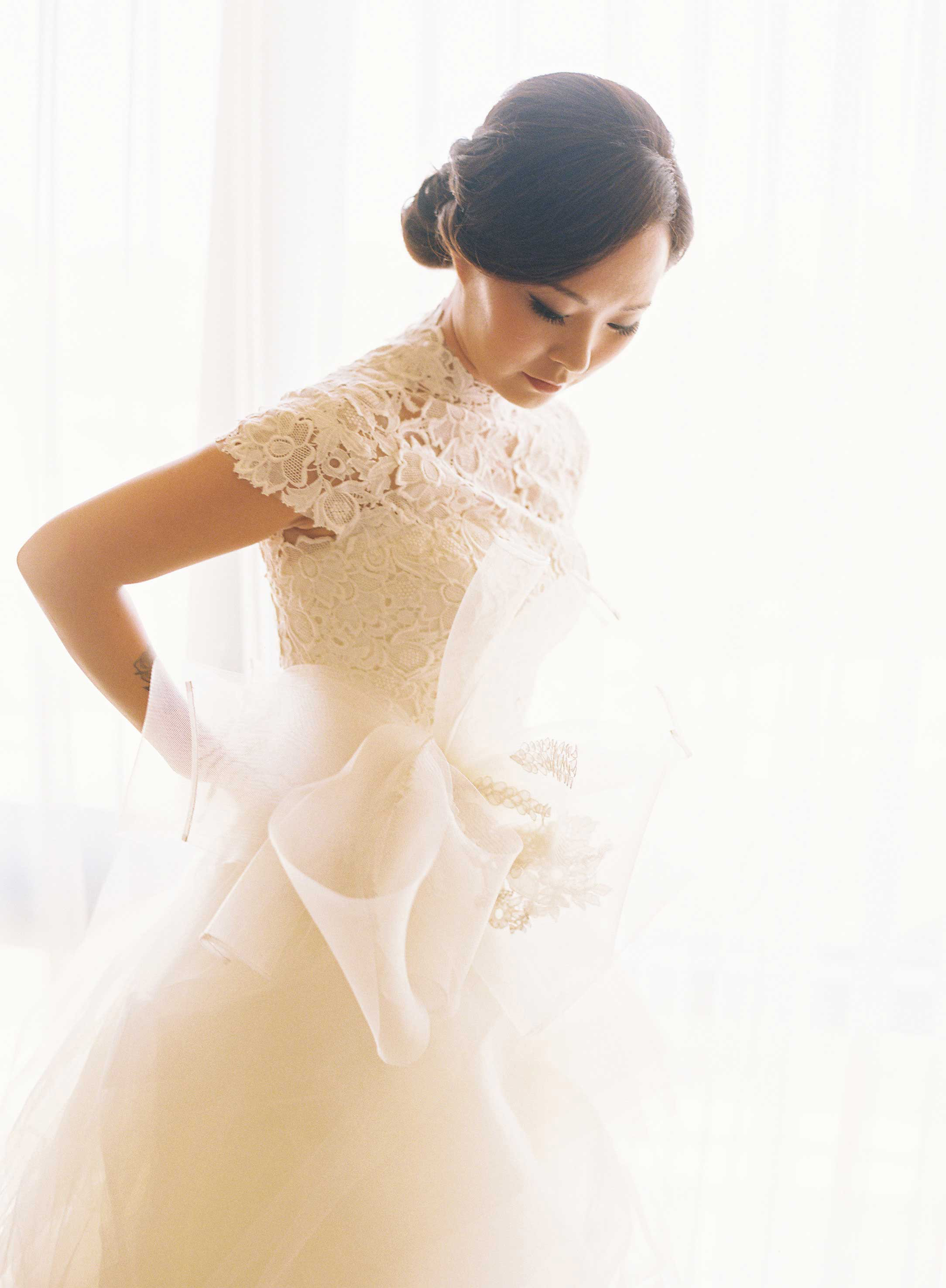 Asian American bride in wedding dress with bow