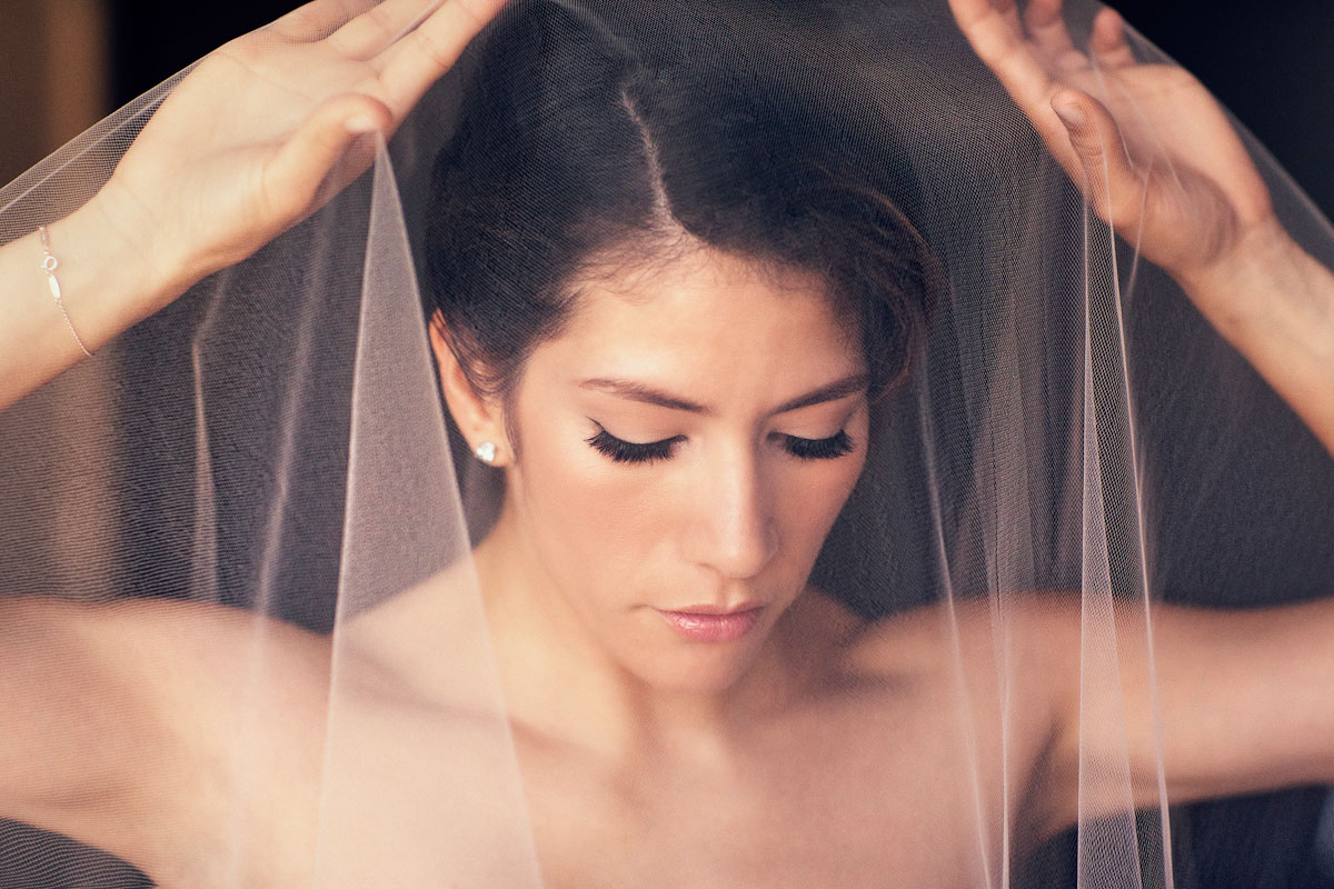 Bride with updo behind wedding veil