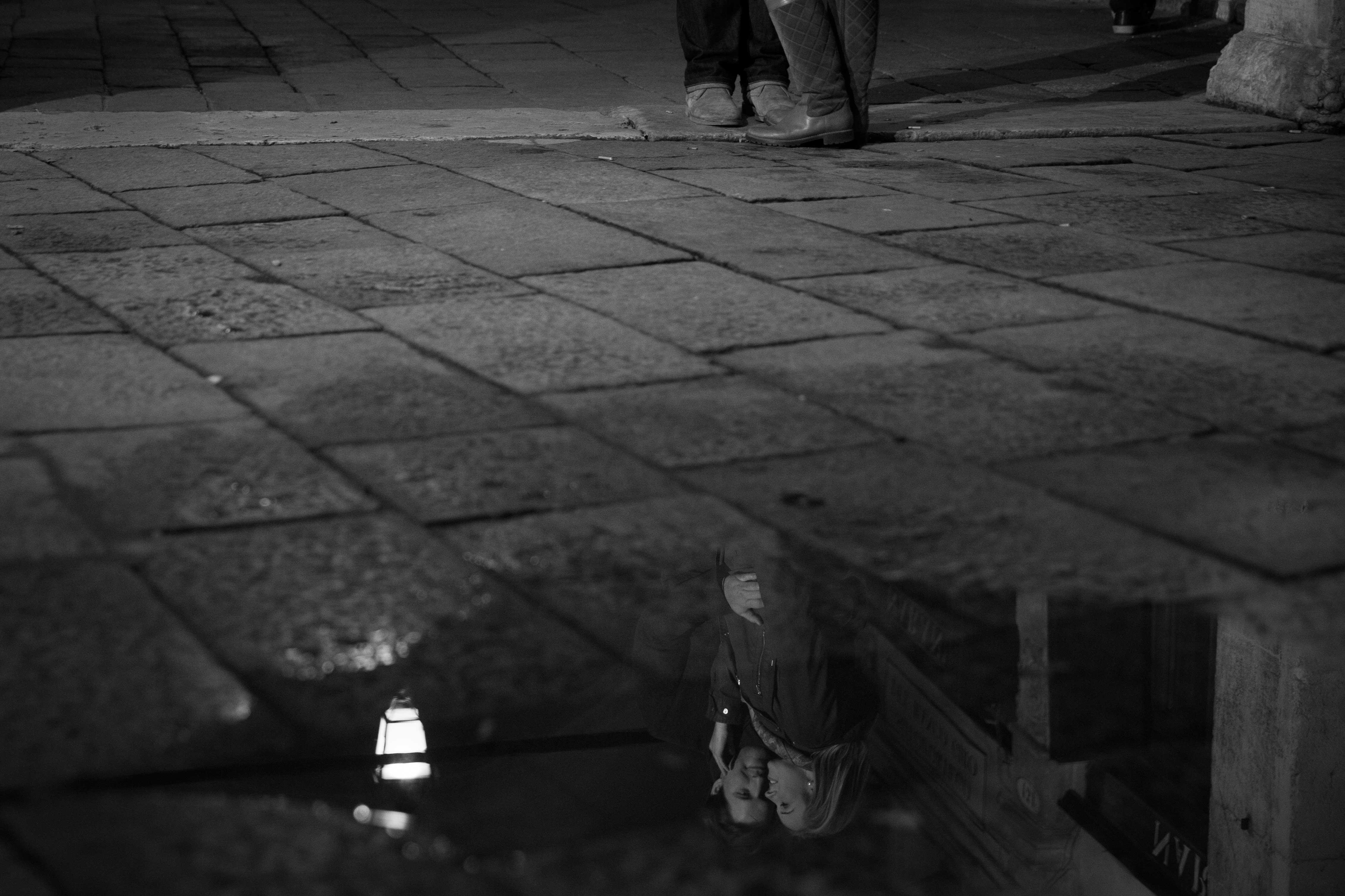Black and white engagement photo of reflection in puddle