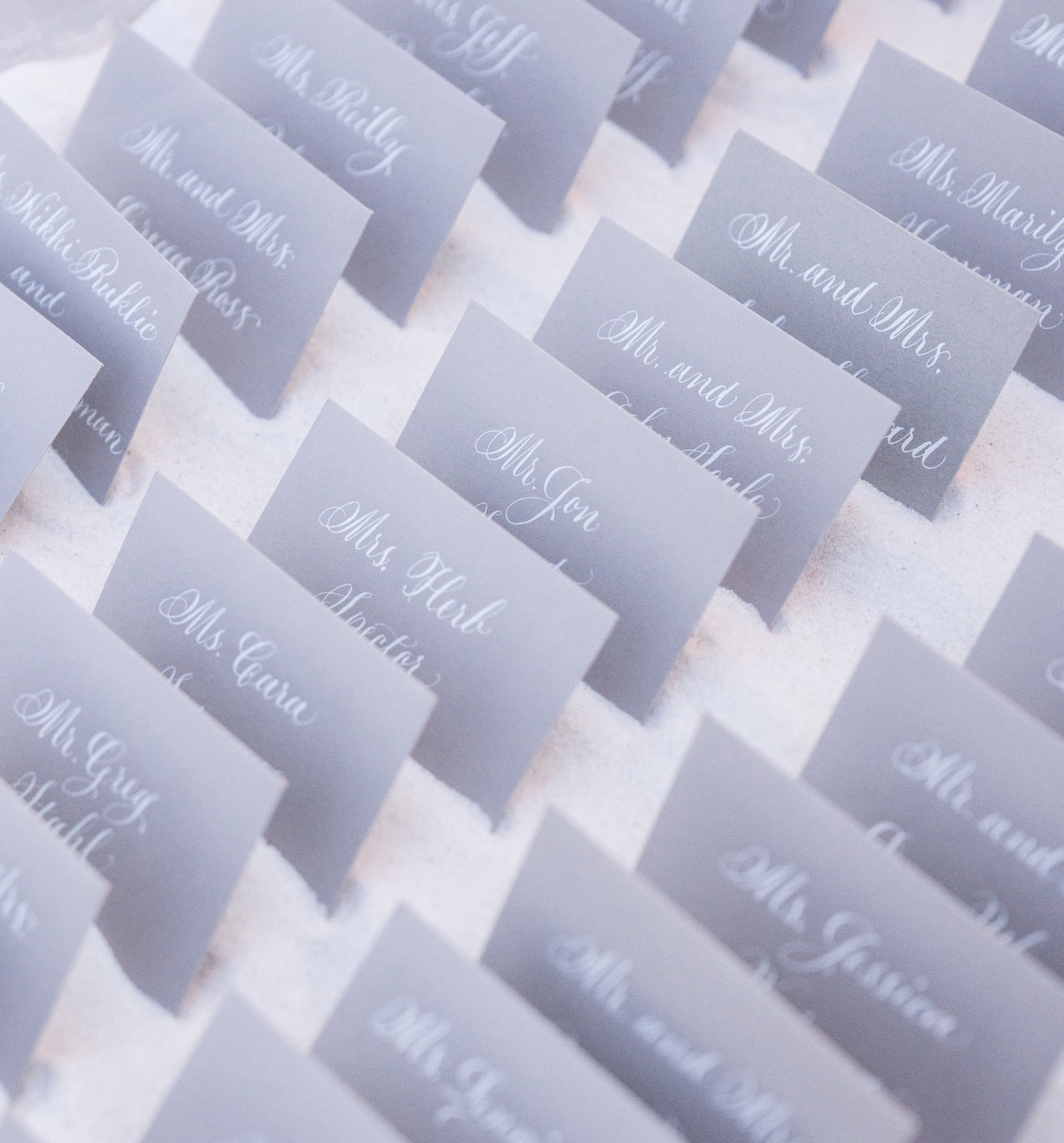 Grey escort cards for wedding with white calligraphy