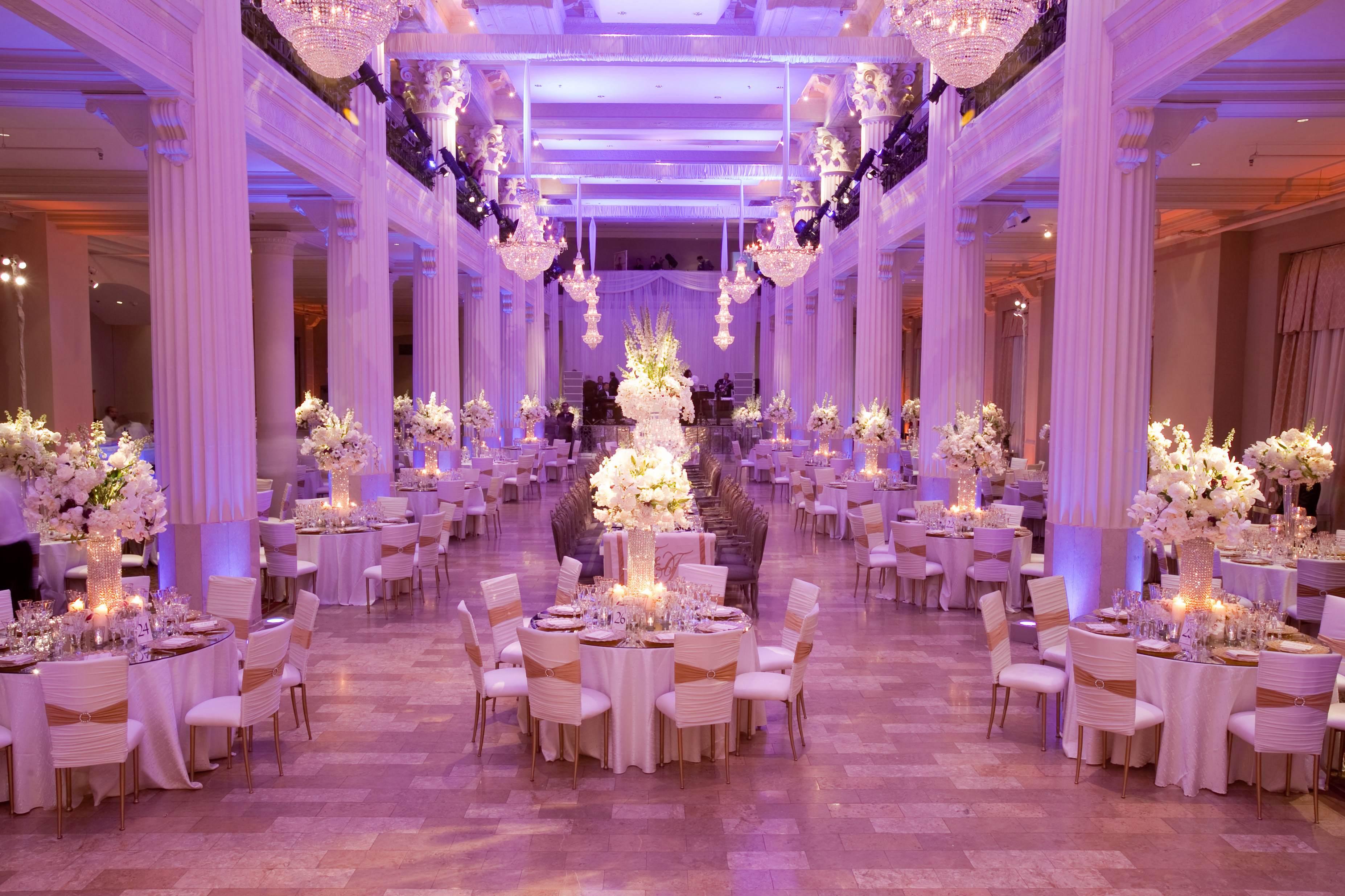 Purple lighting at ballroom wedding reception with columns