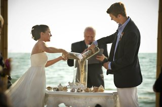 bride-and-groom-pouring-sand-in-glass-vessel