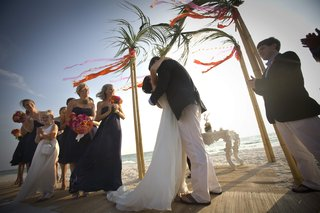 couple-kissing-on-sand-at-beach-wedding