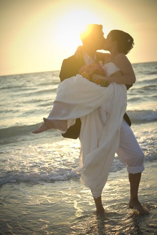 bride-and-groom-sharing-a-beachside-sunset-kiss