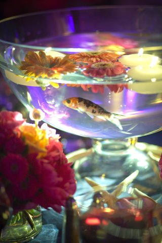 spotted-fish-swimming-in-bowl-of-candles-and-flowers