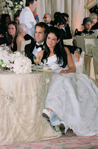 bride-in-a-strapless-gown-and-groom-in-black-tuxedo-sitting-at-their-reception