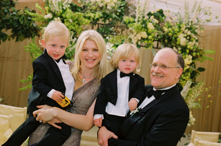 woman-in-floral-dress-and-man-in-a-black-tuxedo-holding-little-boys-dressed-in-tails