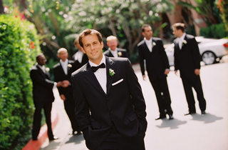 groom-in-a-black-tuxedo-with-a-matching-bow-tie-and-a-white-boutonniere-and-pocket-square