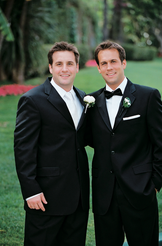 best-man-wearing-a-black-tuxedo-with-a-white-tie-and-rose-boutonniere
