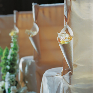 paper-cones-filled-with-rose-petals-and-hung-from-chairs-for-a-wedding