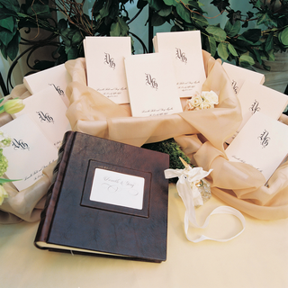 leather-bound-wedding-guest-book-and-golden-pen-wrapped-with-white-ribbon