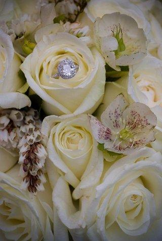 diamond-halo-wedding-ring-on-bed-of-white-roses