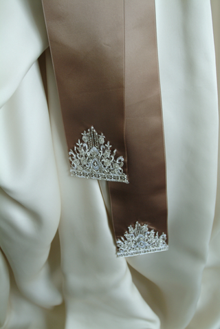 close-up-of-brown-ribbon-sash-with-embroidery-at-ends