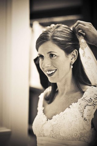 sepia-tone-photo-of-bride-getting-veil-pinned-on-her-hair