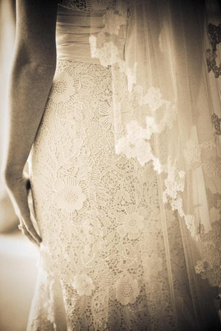 sepia-tone-image-of-spring-wedding-lace-bridal-gown-skirt-details