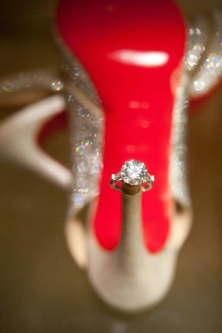 round-diamond-engagement-ring-on-heel-of-christian-louboutin-red-sole
