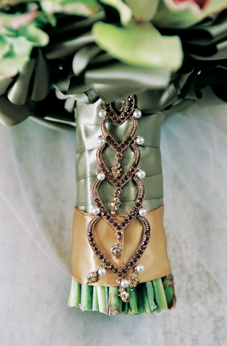 stems-of-bouquet-wrapped-with-ribbon-and-cascading-jewel-pendant
