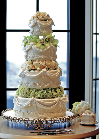 four-layer-cake-topped-with-orchid-and-rose-flowers-and-sugar-drapery