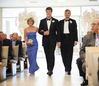groom-walks-down-aisle-with-mom-and-dad-in-church