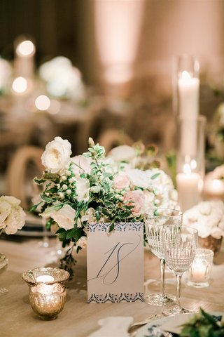 wedding reception white pink rose greenery flowers crystal glassware blue white wedding table number