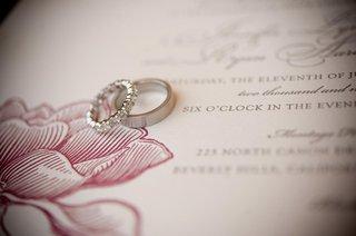 platinum-wedding-rings-on-pink-wedding-invitation