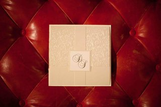 cream-invitation-front-with-monogram-on-red-tufted-background