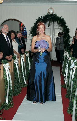 bridesmaid-walks-down-ceremony-aisle-in-blue-dress