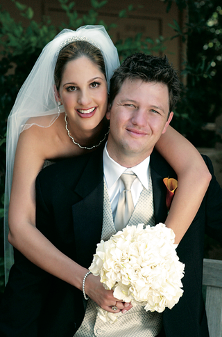 bride-hugs-groom-with-ivory-bouquet