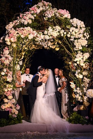 bride-and-groom-kissing-under-floral-chuppah