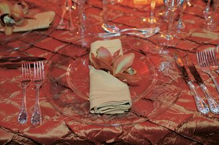 wedding-table-decor-with-silk-amber-tablecloths-clear-chargers-and-an-orchid-in-the-napkin