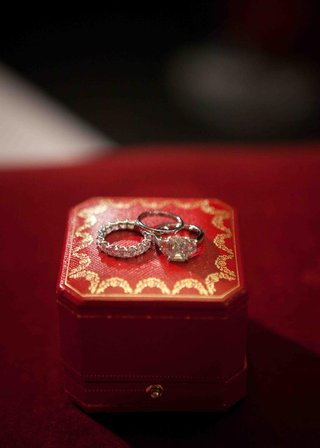 engagement-ring-and-wedding-rings-on-red-and-gold-jewelry-box