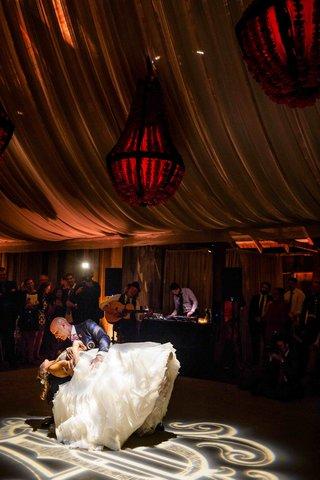 groom-dips-bride-on-dance-floor-at-barn-wedding-reception