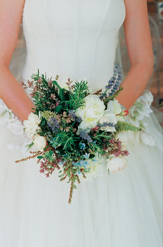 bride-holds-natural-loose-wildflower-bouquet