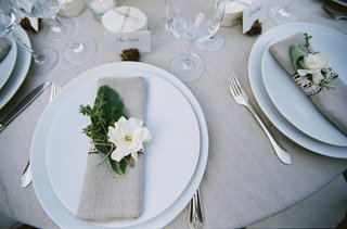 wedding-reception-place-setting-with-flax-napkin-and-herbs-and-gardenia