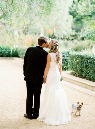 bride-in-a-monique-lhuillier-gown-kisses-groom-in-a-black-tuxedo
