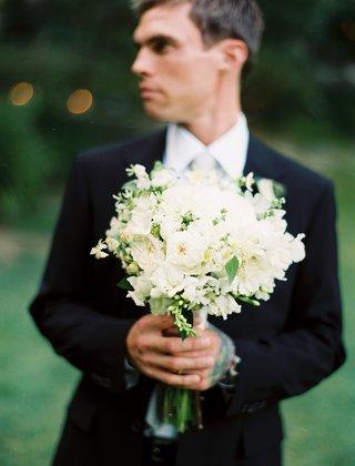 groom-in-black-tuxedo-holds-bouquet-of-white-flowers
